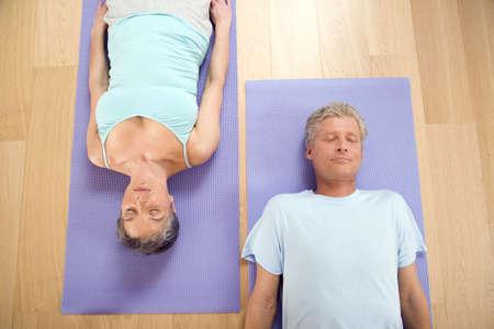 interiour shots: Mature couple on gymnastic mat, smiling, portrait LANG_EVOIMAGES