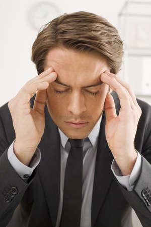 overstress: Businessman sitting, hands to head, portrait