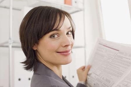 Businesswoman reading newspaper, portrait LANG_EVOIMAGES