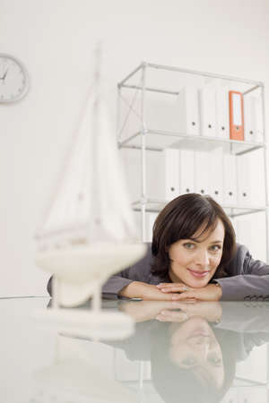 interiour shots: Businesswoman looking at ship model