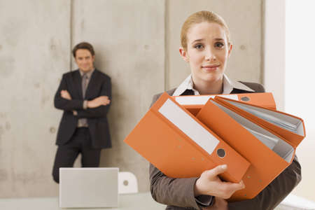interiour shots: Businesswoman carrying folders, businessman in the background LANG_EVOIMAGES