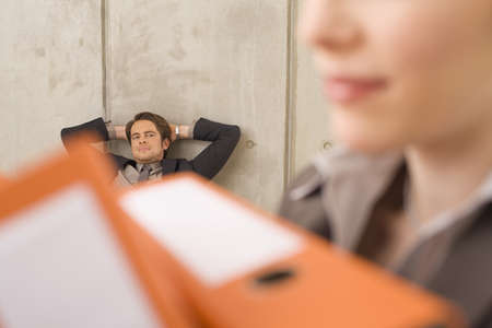 overstress: Businesswoman carrying folders, businessman in the background LANG_EVOIMAGES