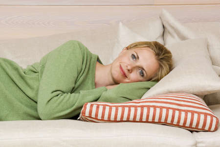 Young woman relaxing on sofa, smiling, portrait Stock Photo - 23891406