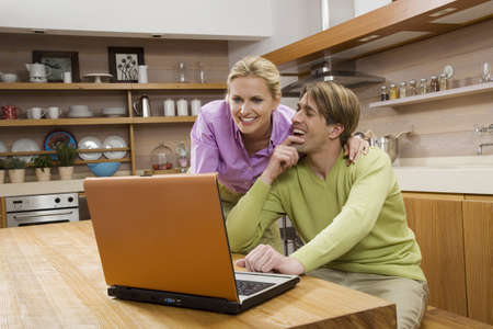 interiour shots: Young couple in kitchen, using laptop, portrait
