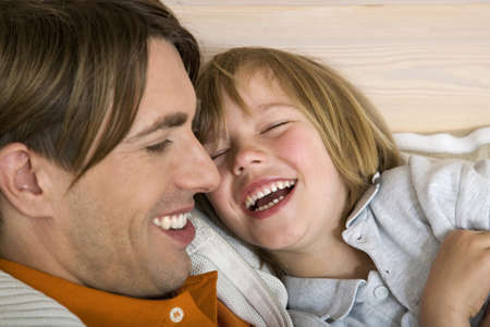 interiour shots: Fahter and son (8-9) laughing, close-up, portrait