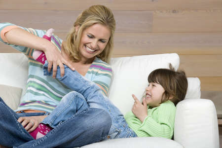 Mother and daughter (6-7) sitting on sofa, portrait Stock Photo - 23891425