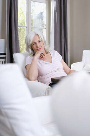 50 to 60: Senior woman sitting in living room, portrait LANG_EVOIMAGES