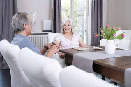 55 59 years: Senior couple sitting at table in living room, smiling, portrait