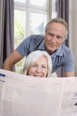 age 50 55 years: Senior Woman holding a newspaper, senior man behind, portrait