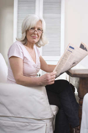 Senior woman holding newspaper, portrait Stock Photo - 23891440