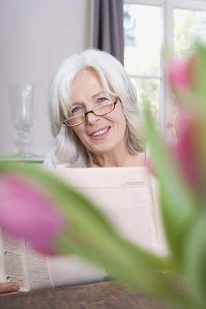 Senior woman holding newspaper, smiling, portrait Stock Photo - 23891441