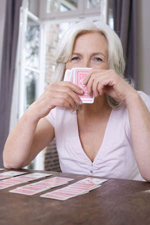 55 59 years: Senior woman playing Solitaire, portrait