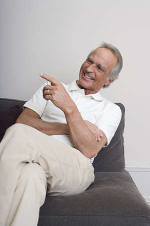 60 64 years: Senior man on sofa, smiling, portrait
