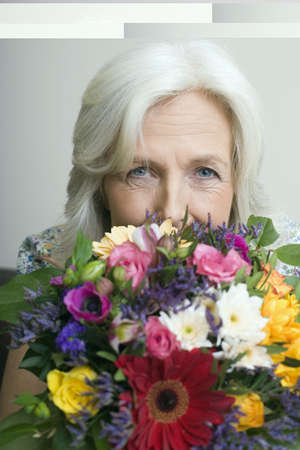 55 59 years: Senior woman holding bunch of flowers, portrait