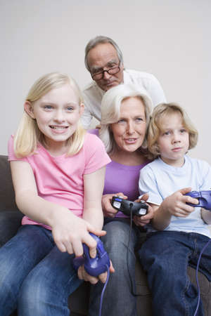 55 59 years: Grandparents and grandchildren (8-9) playing video game, portrait