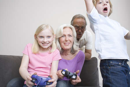 Grandparents and grandchildren (8-9) playing video game, portrait Stock Photo - 23891468