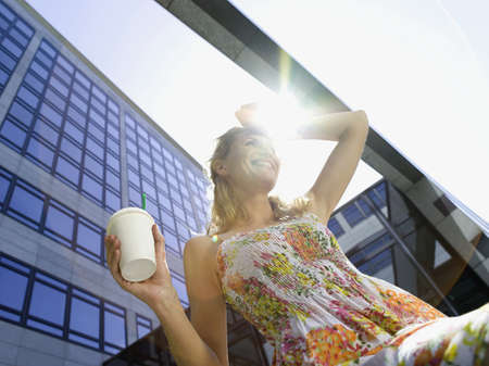 Germany, Baden-Württemberg, Stuttgart, Young businesswoman taking a break, drinking coffee, low angle view