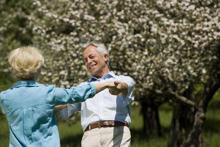 65 69 years: Germany, Baden Württemberg, Tübingen, Senior man and woman holding hands, dancing happily