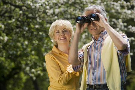 65 69 years: Germany, Baden Württemberg, Tübingen, Senior couple, senior man looking through binoculars