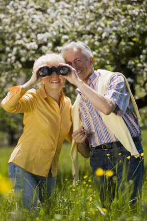 65 69 years: Germany, Baden Württemberg, Tübingen, Senior couple, senior woman looking through binoculars