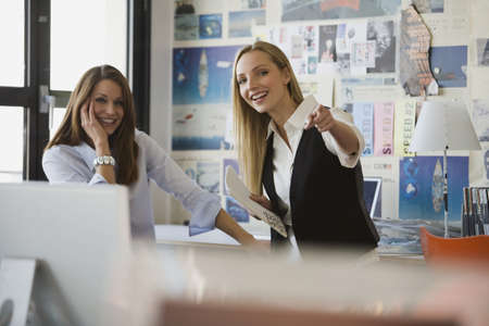 interiour shots: Two women in office, smiling LANG_EVOIMAGES