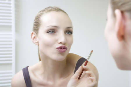 puckering lips: Young woman holding lip brush, puckering lips