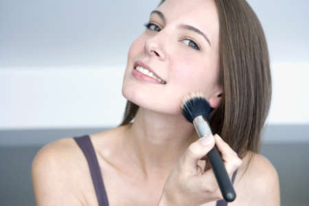 interiour shots: Young woman using make-up brush, portrait, close up