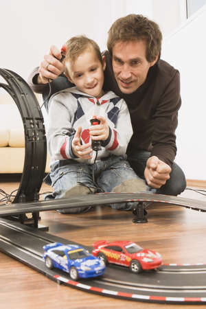 looping: Father and son (4-5) playing with toy racetrack