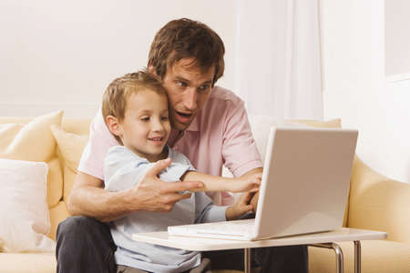 Father and son (4-5) using laptop Stock Photo - 23891533