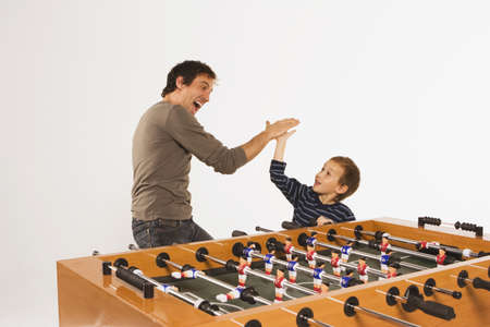 foosball: Father and son (4-5) at tabletop soccer, slap hands LANG_EVOIMAGES