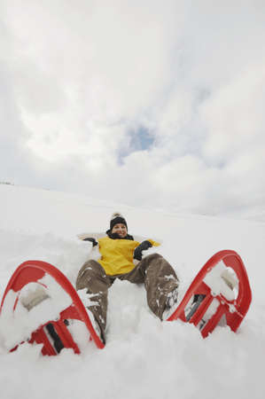 snowshoes: Italy, South Tyrol, Young woman with snowshoes lying in snow