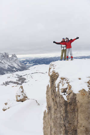 mountaintops: Italy, South Tyrol, Couple in winter clothes on mountain top, cheering LANG_EVOIMAGES