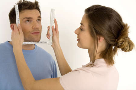 Woman measuring man's face with ruler, smiling, close-up Stock Photo - 24276858