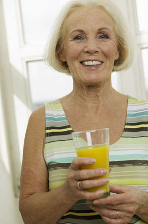 kind hearted: Senior woman holding glass of juice, smiling, close-up, portrait