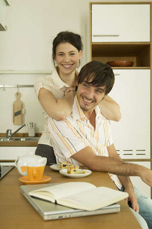 confiding: Young couple in kitchen,smiling LANG_EVOIMAGES
