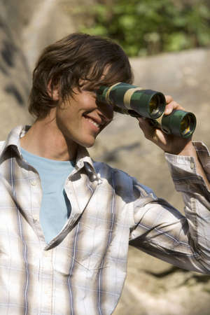 Young man looking through binoculars,smiling Stock Photo - 24276864