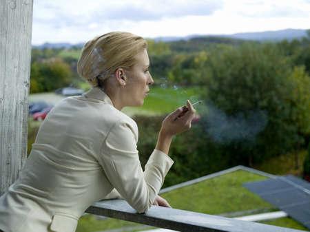30 35 years women: Businesswoman smoking on balcony