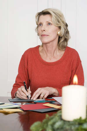 profundity: Woman writing Christmas cards, looking away, portrait