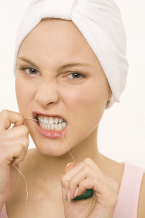 interiour shots: Close-up of a young woman flossing her teeth