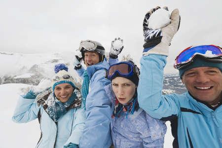 ropa de invierno: Italia, Tirol del Sur, Cuatro personas en ropa de invierno, sosteniendo bolas de nieve