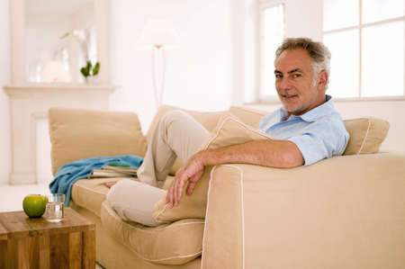50 to 60 years: Mature man sitting on sofa in living room,portrait