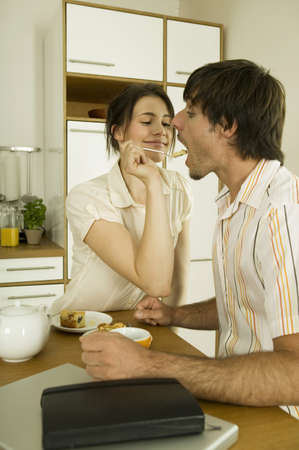 Young couple in kitchen,woman feeding man Stock Photo - 24303112