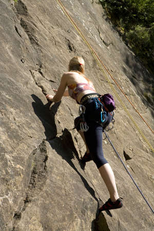 straining: Young woman rock climbing,low angle view