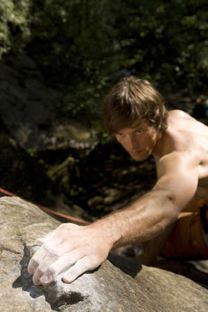 non moving activity: Young man rock climbing,focus on hand,close-up LANG_EVOIMAGES