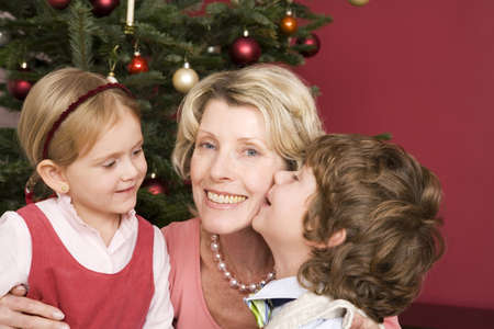 Grandmother embracing grandchildren on Christmas Eve Stock Photo - 24303121