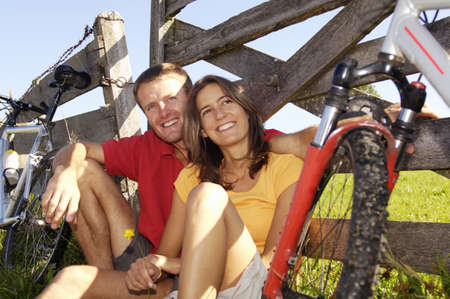 Couple sitting in meadow, leaning on wooden railing Stock Photo - 24303123