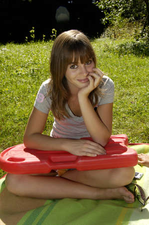 age 16 17 years: Teenage girl (16-17) sitting in meadow, holding float