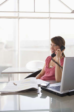 Woman at desk using phone Stock Photo - 24303133