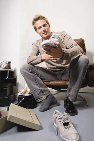 comprando zapatos: Hombre joven en la tienda de zapatos, tratando de zapatos