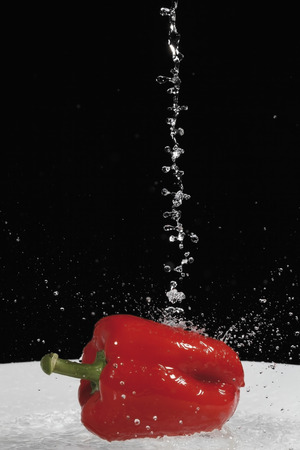 Red bell pepper under jet of water, close up photo